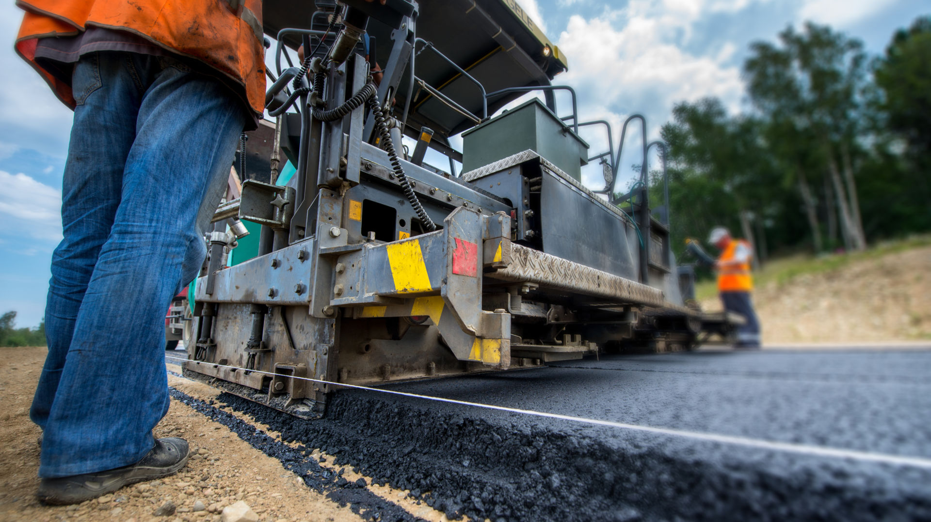 workers laying bitumen on a road