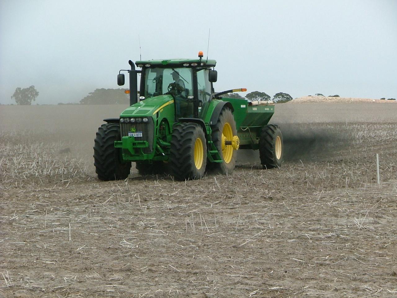 spreading biochar onto soil with a fertiliser spreader